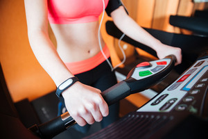 Treadmill used by young sportswoman with fitness tracker on  hand