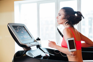 Woman running on treadmill in gym and listening to music