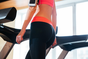 Beautiful young sportswoman using treadmill in gym