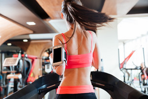 Woman athlete with balnk screen smartphone running on treadmill