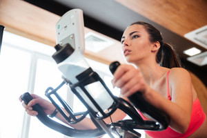 Focused sportswoman exercising on bicycle in gym