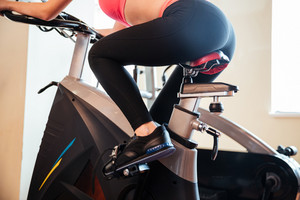 Attractive young woman athlete training in gym using bicyle