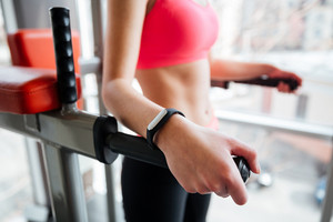 Woman athlete with fitness tracker on hand working out