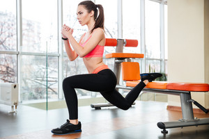 Sportswoman doing squats using bench in gym