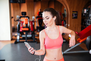 Smiling woman athlete with earphones using smartphone in gym