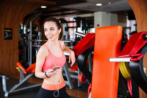 Cheerful sportswoman listening to music from mobile phone in gym