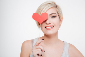 Smiling woman holding red heart