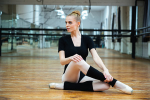 Beautiful ballerina sitting on the floor