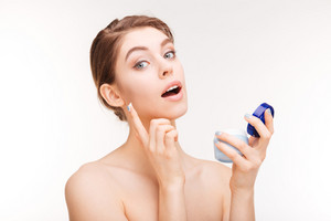 Charming woman using facial cream