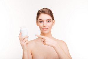 Woman pointing finger on bottle with pills