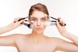 Beauty portrait of pretty young woman posing with makeup brushes