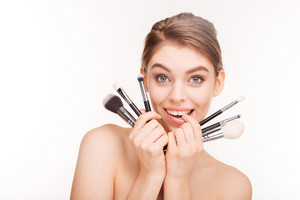 Beauty portrait of cute lovely young woman holding makeup brushes