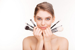 Beauty portrait of pretty smiling young woman with makeup brushes
