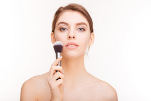 Beauty portrait of sensual charming young woman holding makeup brush