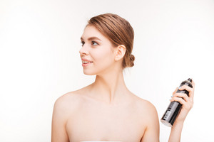 Beauty portrait of happy woman applying hairspray on her hair