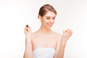 Portrait of beautiful young woman painting her nails