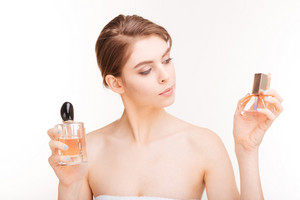Attractive young woman holding two bottles of parfums