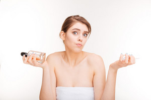 Beauty portrait of confused young woman choosing between two parfums