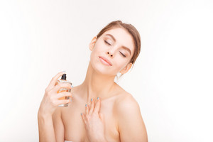 Sensual woman with closed eyes applying parfume on her neck
