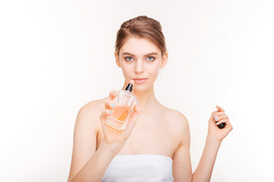 Beautiful young woman with bottle of parfum