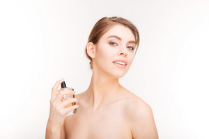 Beauty portrait of attractive young woman applying parfum