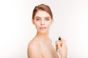 Pretty young woman holding bottle of parfume