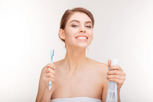 Beauty portrait of cheerful young woman with toothpaste and toothbrush