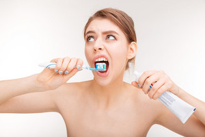 Pretty young woman using toothpaste and brushing her teeth