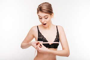Happy surprised young woman in lace bra measuring her bust