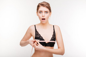 Amazed stunned young woman in black bra measuring her chest