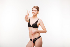 Cheerful woman showing victory sign and measuring her waist