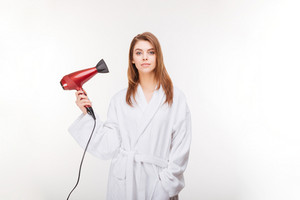 Attractive young woman in bathrobe standing and holding hair dryer