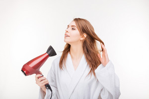 Pretty smiling young woman in bathrobe using hair dryer