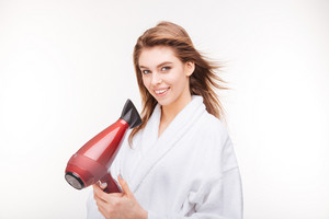 Happy attractive woman in bathrobe standing and using hair dryer