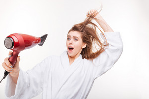 Funny frightened young woman drying hair and scared of dryer