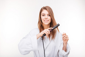 Beautiful happy young woman in bathrobe using hair straightener