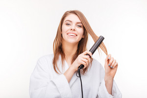 Cheerful attractive young woman straightening her hair with  straightener