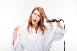 Scared pretty young woman in bathrobe using hair straightener