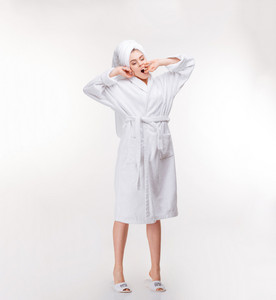 Relaxed woman with towel on her head stretching and yawning