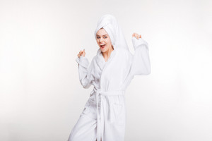 Happy excited woman dancing in bathrobe with towel on head