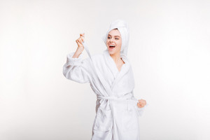 Cheerful joyful young woman in bathrobe with towel on head