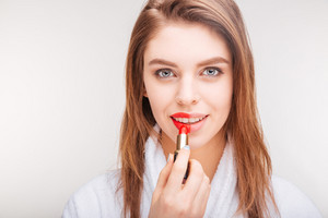 Attractive happy woman applying red lipstick on part of lip