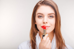 Beautiful smiling young woman in bathrobe using red lipstick