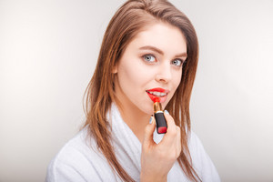 Attractive lovely young woman testing red lipstick on her lips
