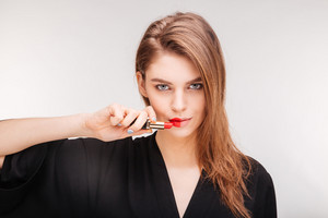 Beautiful woman showing color of lipstick on her lips