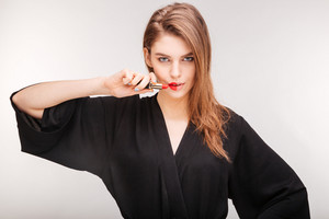 Gorgeous woman demonstrating red lipstick on half of her lips