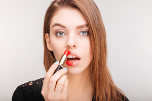 Beauty portrait of pretty woman doing makeup with red lipstick