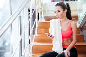 Happy charming sportswoman listening to music from smartphone in gym