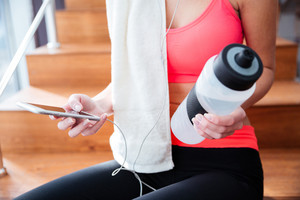 Sportswoman holding cell phone and bottle of water in gym
