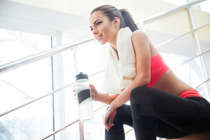 Happy beautiful sportswoman drinking water on stairs in gym